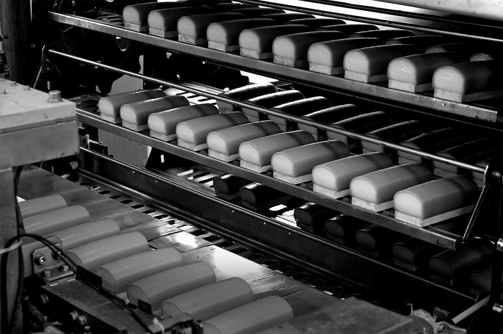機械によって成形された蒲鉾が、大型の蒸機に運ばれる様子