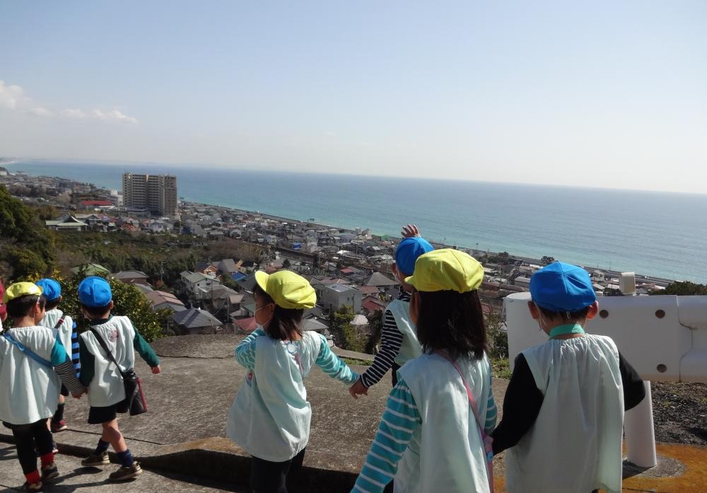 丘から小田原の街と海を見ている園児たち
