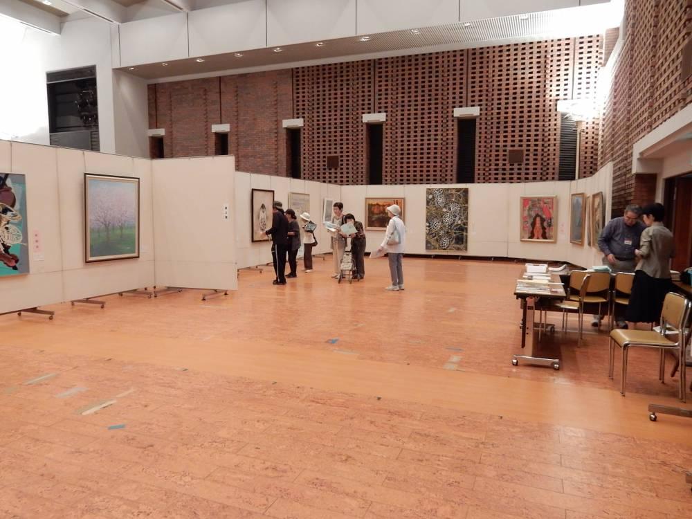 生涯学習センターけやきでの展示会場。広い会場で数人の客が作品を眺めているようす。