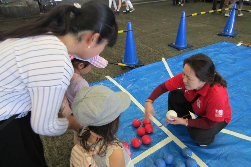 ボッチャのボールの説明をうける子供