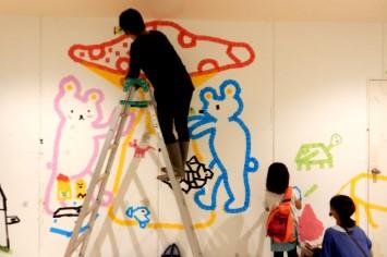カラーテープで親子で壁に絵を描いている様子