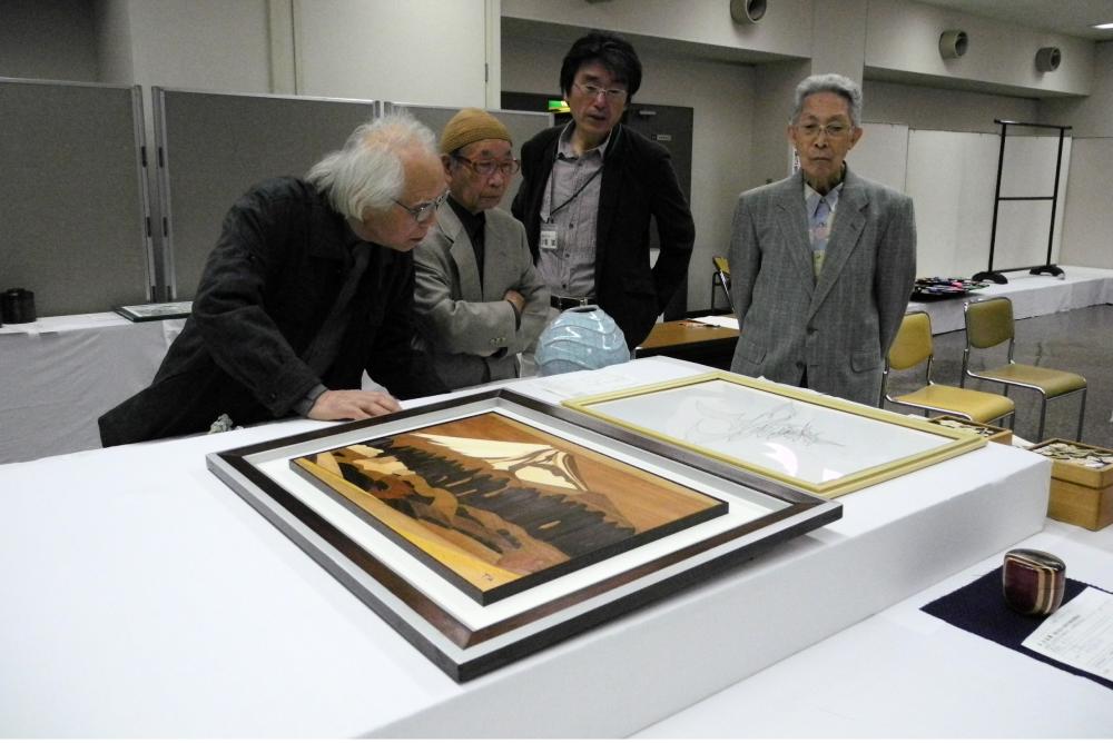 4人の先生が工芸作品に対して協議・審査をしている風景