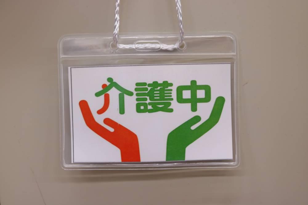 介護中を示す「介護マーク」。オレンジと緑のカラーで、支えあうようすがデザインされている。