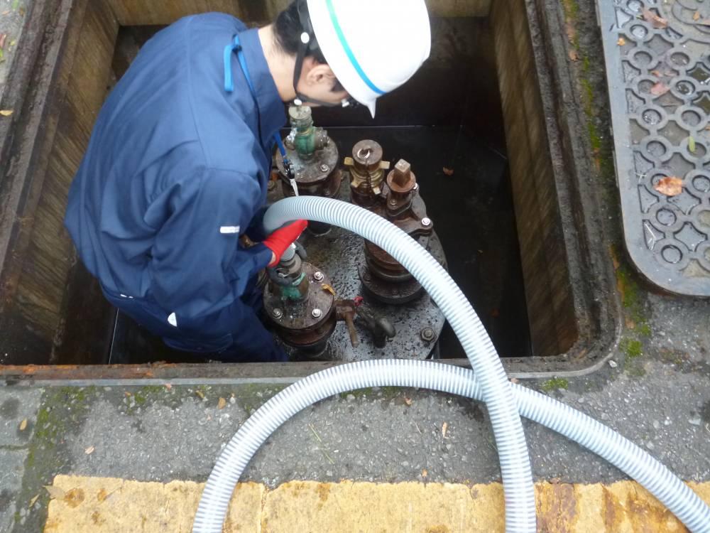 耐震性貯水槽から水を汲み出すポンプを接続する様子