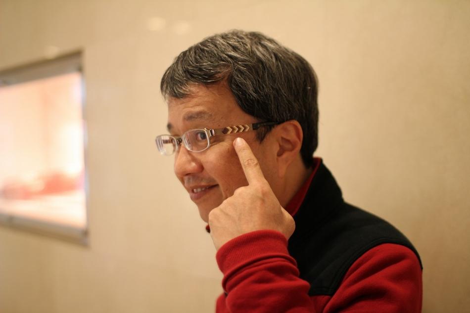 寄木細工のメガネをかける小宮孝泰さん